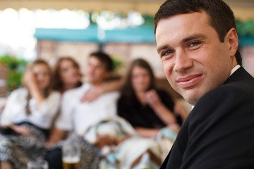 Man smiles over his shoulder surrounded by friends