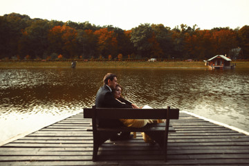 Man and woman rest on the bench at the lake