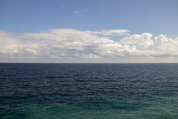The dark sea water and sky with clouds, visible horizon