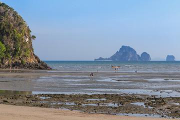 Tourists walking in shallow water during low tide at aonang beach, Krabi, Thailand