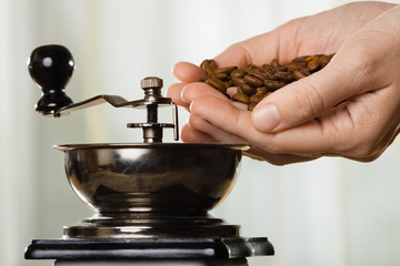 hand with coffee beans and grinder