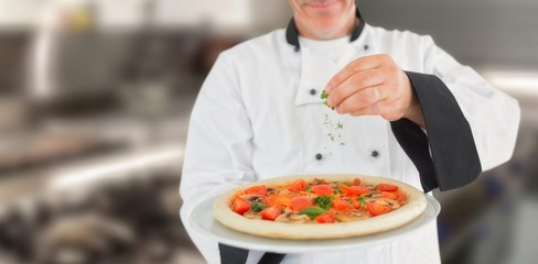 Composite image of portrait of a chef holding a pizza and adding