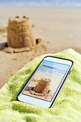 picture of a sandcastle in a smartphone on the beach