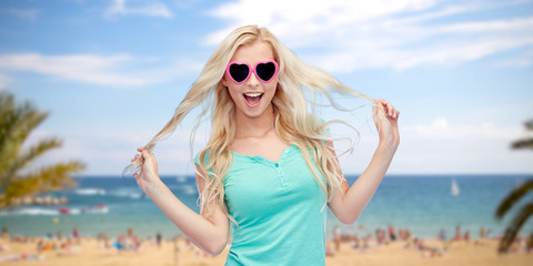 happy young blonde woman or teenager in sunglasses