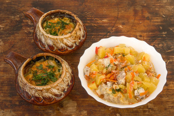 Roast pork, potatoes and carrots in a clay pot on the wooden background