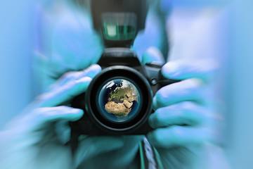 Planète terre et le réchauffement climatique , observation, photographie appareil photo avec photographe, objectif  effet flou, vue satellite bleu clair