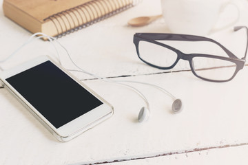 cellphone and earphone with a cup of coffee