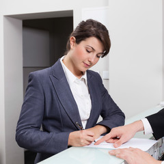 Horizontal view of attractive businesswoman signing document