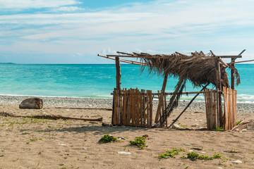 Bamboo fisherman hut on the seashore on sunny day.