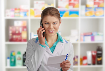 Friendly female pharmachist consulting patient via phone in drug store. Concept of medicine and health.