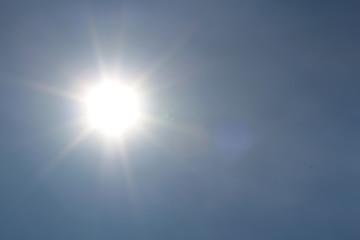 Sonne scheint am blauen Himmel