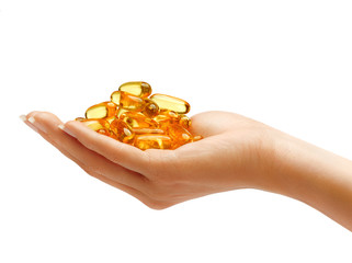 Woman's Hand holding Omega 3 capsules isolated on white background. Palm up, close up. High resolution product.
