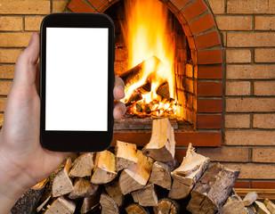 tourist photographs fireplace on smartphone