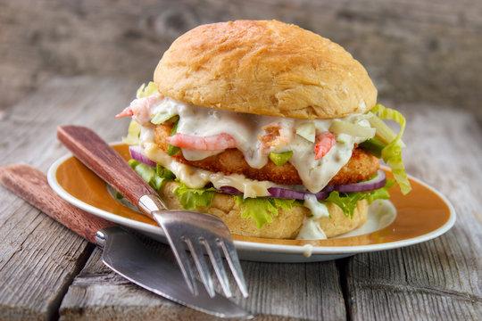 Salmon and shrimp burger , mayonnaise on bottom bun , breaded salmon shrimp patty and tartar sauce with fresh shrimps on gray wooden boards background