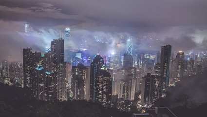 Beautiful view over Hong Kong and Victoria Harbor through the fog, mist and clouds from the best view point Victoria Peak. City lights at night.