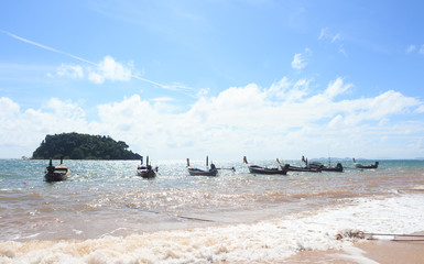 line of arrange fishing boat with rope at beach harbor island in sunny blue sky