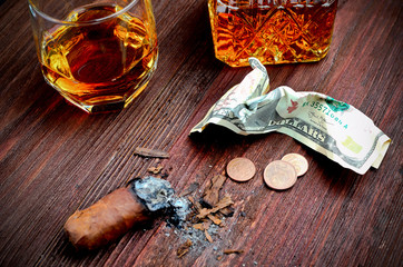 Whisky in a glass with a cigar, money, and a carafe of vintage