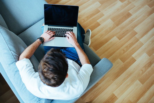 Overhead picture of  man using laptop sitting relaxed on sofa.