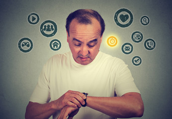 Middle age man using checking time on his smart watch with apps icons. New technology gadget concept