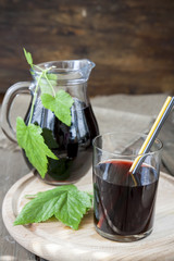 Glass and jug with fresh Black Currant juice decoration fresh currant leaves