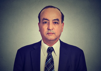Head and shoulders shot of a middle aged business man in a suit and shirt with tie.