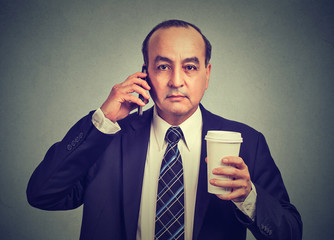 Business man talking on a cell phone holding cup of coffee