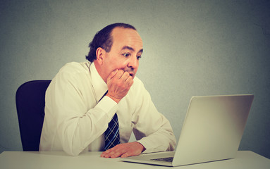 Desperate middle aged employee man working on computer in his office