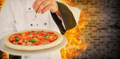 Composite image of close up on a chef holding a pizza