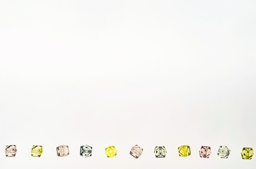 Background with plastic fake jewels on white surface