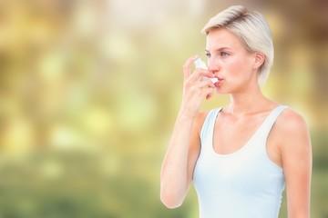Composite image of blonde woman taking her inhaler