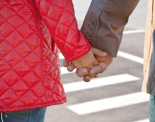 Hands of father and child on a pedestrian crossing, close-up