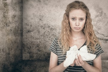 Composite image of sick blonde woman holding paper tissue