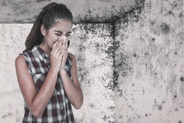 Composite image of sick blonde woman sneezing in a tissue