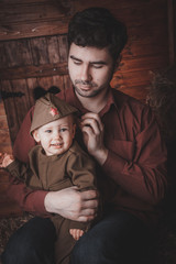 Retro! One year smiling baby dressed in Second World War russian uniform. With father. Wood background