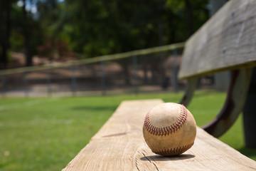 Baseball on a bench in a little league field
