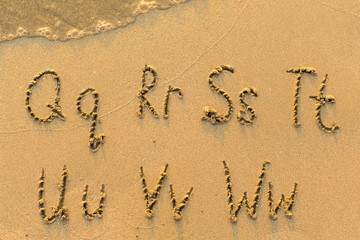 Alphabet written by hand on sandy beach (letters from Q to W)
