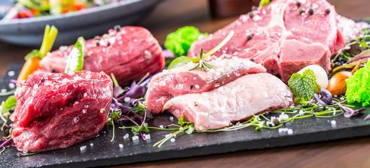 Steak.Beef steak.Meat.Portioned meat.Raw fresh meat.Sirloin steak.T-Bone steak. Flank steak. Duck breast. Vegetable decoration. Portioned meat prepared for processing in a restaurant or hotel kitchen.