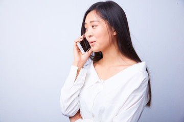 Chinese woman in white talking on a cell phone