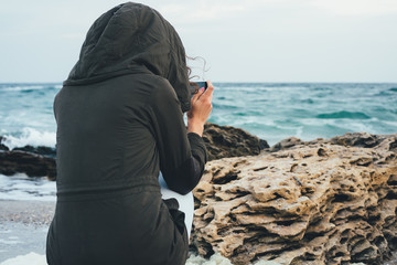 Girl in the green hoodie sitting on the beach photographing the