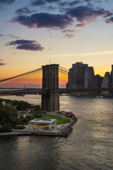 Fotomurales - Sunset over the Brooklyn Bridge and Carousel with view on the Manhattan Lower East Side Financial District. East River. New York City