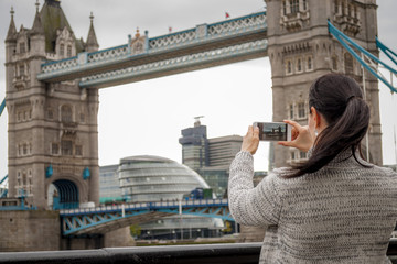 Woman taking pictures of the Tower Bridge with her phone, in London, England, UK