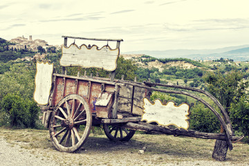 Old wooden cart against vineyards, Tuscany, Italy. Processing in retro style