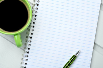 Empty notebook with cup of coffee on table