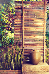 Bamboo fence with plants . plants on a bamboo wall . Landscape design . The design and decoration of the garden