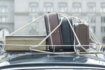 Vintage suitcases on the roof of the trunk of a car.
