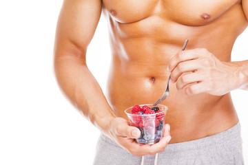 Fit man holding a bowl of fresh red fruits, isolated on white ba