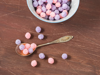 Round purple and pink candies in a bowl on wooden background, copy space