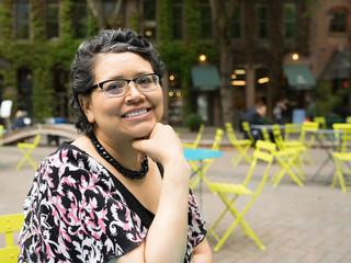 Happy Hispanic Woman In 40's Enjoys Outdoor Dining