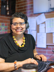 Middle Aged Hispanic Female In Office Environment Wearing Headph