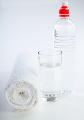 Bottle of water and towel on white background